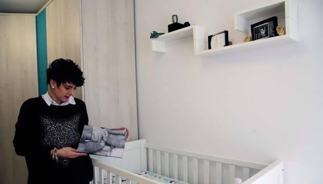 Imagen de la pamplonesa Marta Martínez, de 33 años, observando una fotografía de las manos de su bebé.