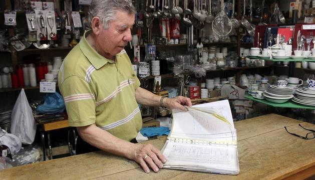 Una persona mayor, en el mostrador de una ferretería repasa papeles sobre su negocio.
