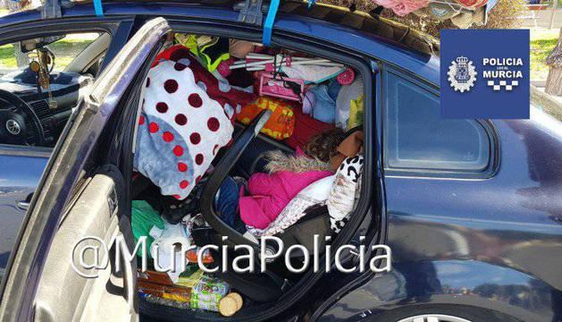 Imagen de la Policía Local de Murcia, con el coche, los enseres y la niña debajo.