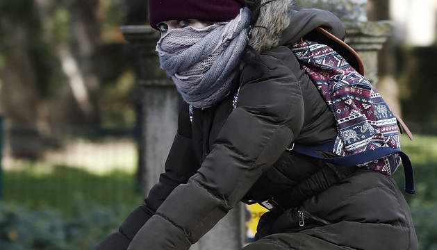 Una joven montada en su bicicleta se protege del frío en Pamplona.