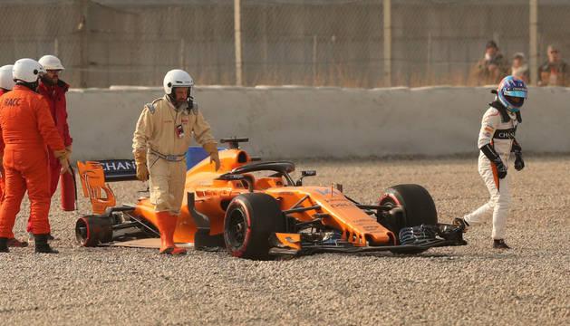 Alonso se aleja de su MCL33 mientras los técnicos de McLaren revisan el eje que ha perdido la rueda