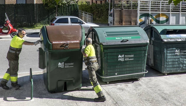 Dos operarios colocan un contenedor de materia orgánica en Mendillorri.