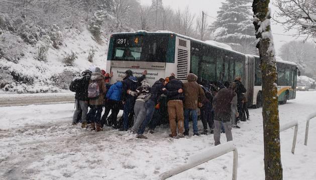 Imagen de varios pasajeros intentando mover una villavesa en la nieve.