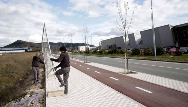 Imagen de operarios colocando el vallado frente a la ciudad deportiva.