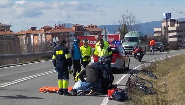 Miembros de los equipos sanitarios de urgencias atienden al ciclista herido en Arre.