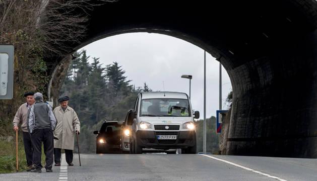 En la imagen, tres personas mayores, dos de ellas con bastón, después de pasar el túnel de Estella delante de una furgoneta que se aproxima a la línea central y les deja mayor espacio.