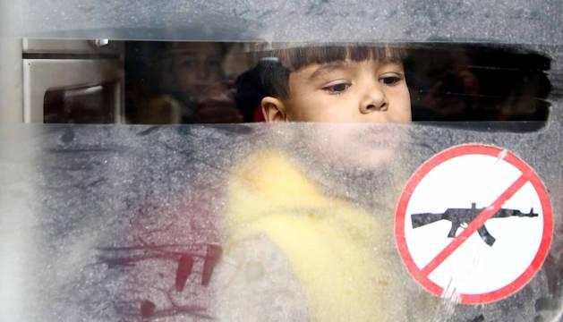 Un niño mira a través de una ventana durante la evacuación