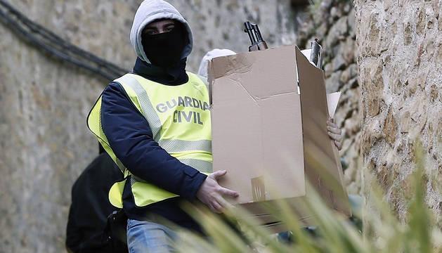 Un agente de la Guardia Civil retira material incautado durante el registro de la vivienda del arrestado en San Martín de Unx.