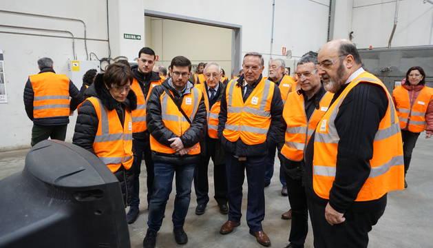 El vicepresidente Laparra, segundo por la derecha, atiende las explicaciones sobre el reciclaje de televisores.