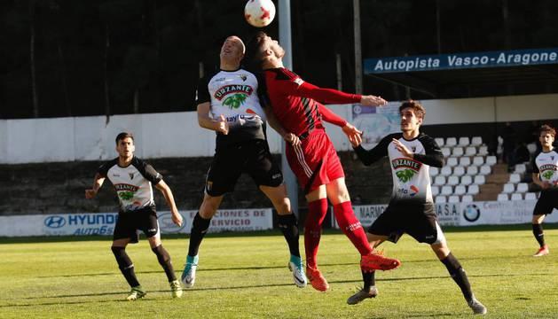 El tudelano Fernando Delgado disputa de cabeza un balón ante un jugador del Arenas en el duelo de ayer.