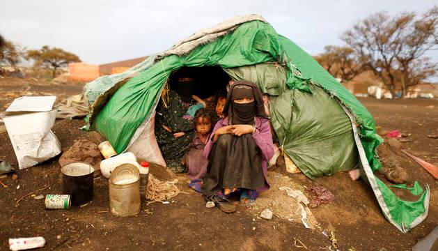 Una mujer y unas niñas, sentadas en una tienda de campaña de un campamento de desplazados por la guerra civil