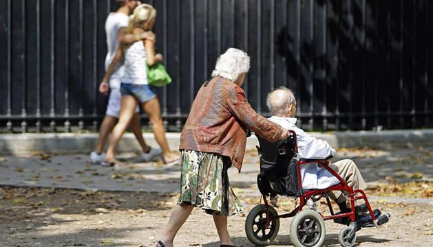 Una mujer empuja la silla de ruedas de un anciano.