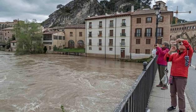 foto de Dos personas realizan en el mediodía de ayer una fotografía de la crecida del río Ega, desde el puente del Azucarero, cuando la bola de la barandilla seguía sumergida.