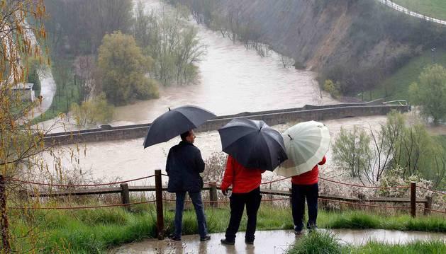foto de Tres personas observan la crecida del río a su paso por Burlada.