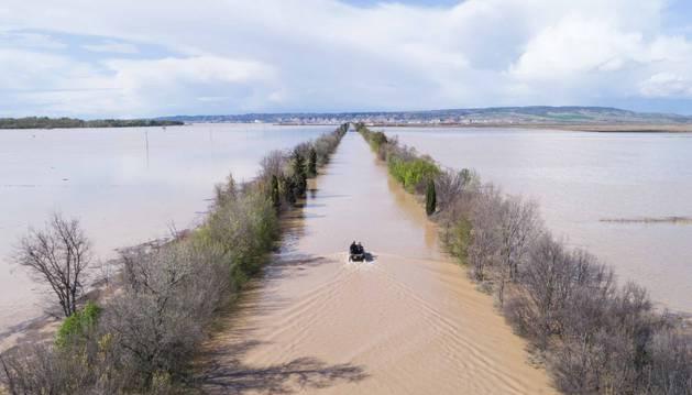 RECTA DE ARGUEDAS Un vehículo pasa por la NA-134 totalmente inundada y con los campos de alrededor anegados.