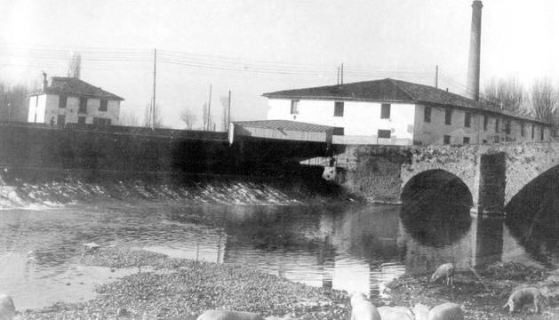 El molino de Santa Engracia, junto a la presa y el puente de su nombre, la Rochapea, en una imagen tomada hacia 1900.