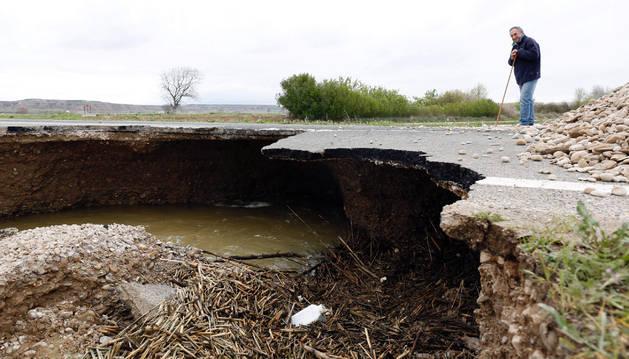 Un hombre observa el hundimiento de la carretera en Buñuel, donde se ve que el agua ha arrastrado su parte inferior