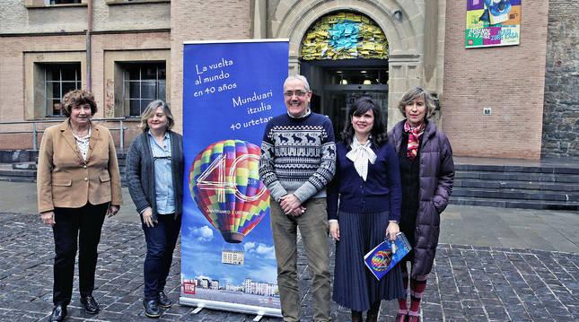 Iosune Aramburu (secretaria), Maite Casero (directora), Patxi Telletxea (vicedirector), Yolanda López (jefa de estudios) y Alicia Otaegui (artista). Al fondo, el tímpano de la EOIP decorado para el aniversario.