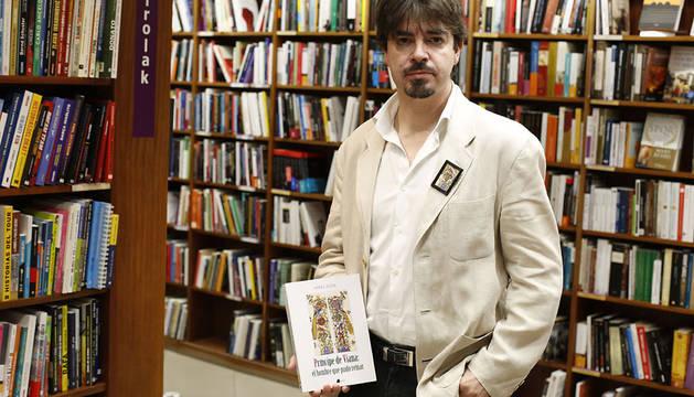 Mikel Zuza, posando ayer en la librería Elkar Comedias con un ejemplar de su libro, Príncipe de Viana: el hombre que pudo reinar.