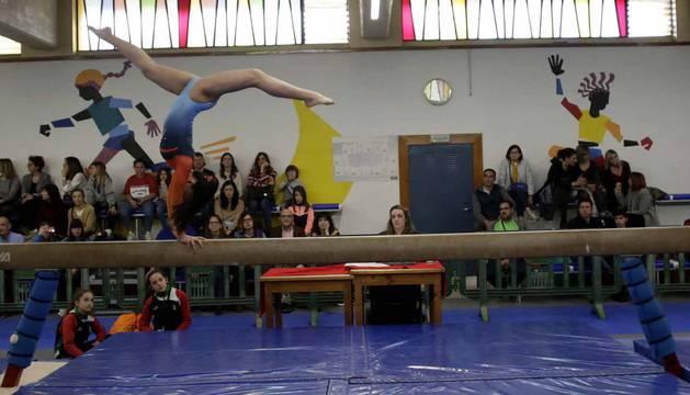 Equilibrio, fuerza, elasticidad y técnicas, claves para poder realizar un ejercicio como el que afrontaba la gimnasta en la barra ante la mirada de público y otras competidoras.