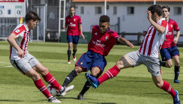 Antonio Otegui busca sacar la pelota ante dos rivales del Bilbao Athletic