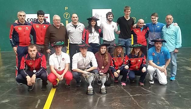 Miguel Pozueta, junto con los pelotaris y técnicos de la Federación Navarra de Pelota ayer en el frontón Ogueta de Vitoria, con los trofeos.