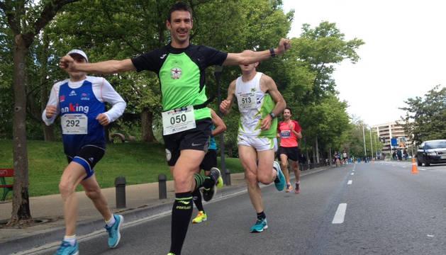 Uno de los participantes saluda durante la Media Maratón Ciudad de Pamplona.