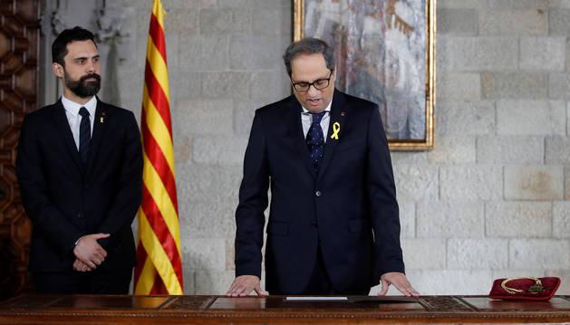 Quim Torra (d), acompañado por el presidente del Parlament, Roger Torrent (i), toma posesión de su cargo como presidente de la Generalitat