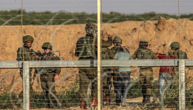 Soldados arrestan a dos palestinos que intentaban saltar a territorio israelí durante enfrentamientos con manifestantes el 15 de mayo de 2018.