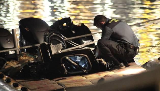 Imagen de un agente de la Guardia Civil, junto a la lancha incautada.