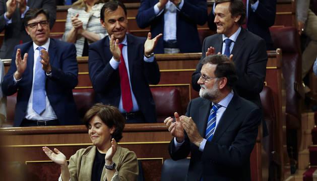 El presidente del Gobierno, Mariano Rajoy (d) y la vicepresidenta, Soraya Sáenz de Santamaría aplauden tras la aprobación de los Presupuestos Generales del Estado para 2018