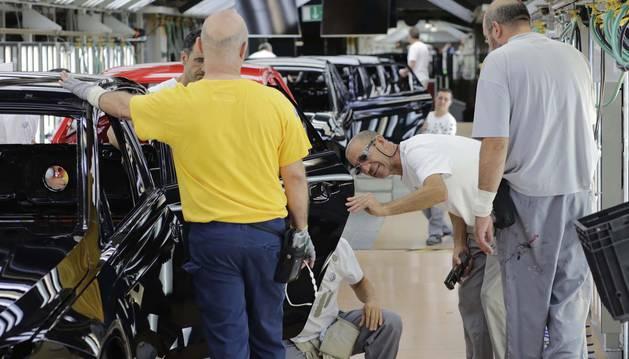 Operarios trabajan con una carrocería en la fase de revisión del taller de pintura.