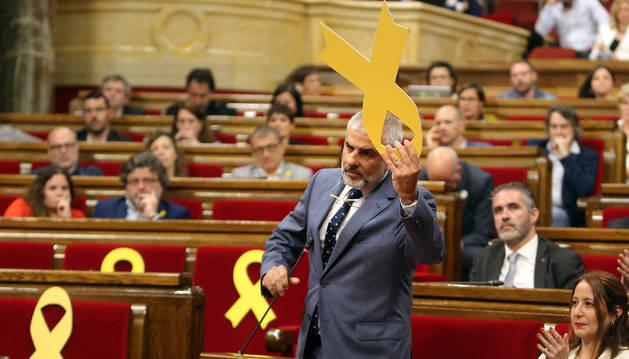 El portavoz del grupo parlamentario de Ciudadanos, Carlos Carrizosa, retiró un lazo amarillo colocado en el banco del Govern, durante el pleno del Parlament
