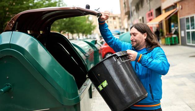 Aitor López introduce en el contenedor residuos orgánicos de la frutería Marian, en la calle Luis Morondo de Azpilagaña.