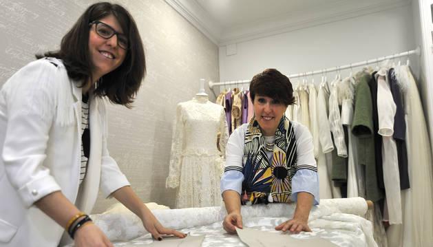 La diseñadora Amaia Artieda, junto a su madre, Patricia, en su 'atelier' de Tafalla con sus colecciones al fondo.