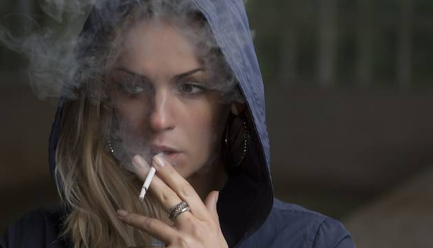Una joven fuma un cigarro