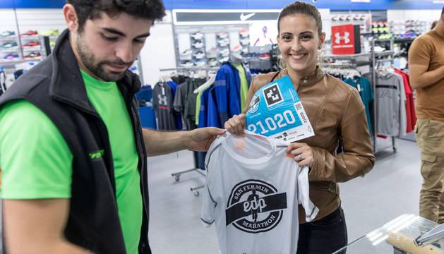 Pablo Zuñiga entrega el dorsal y la camiseta a una participante.