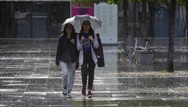 Dos mujeres caminan bajo la lluvia, estos días, en Pamplona.