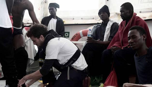 Un miembro del equipo de Médicos sin Fronteros comprueba el estado físico de uno de los inmigrantes