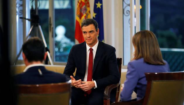 El presidente del Gobierno, Pedro Sánchez (c), acompañado por los presentadores Ana Blanco (d) y Sergio Martín, al comienzo de la entrevista que concede a TVE