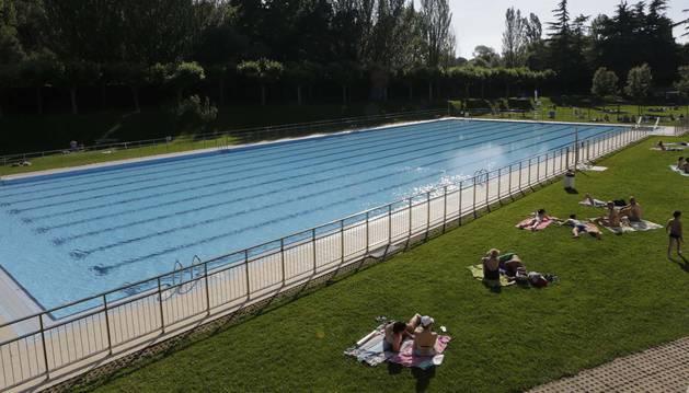 Aspecto de las piscinas de Burlada. El césped lleno de personas tomando el sol. La piscina vacía por la huelga de servicios.
