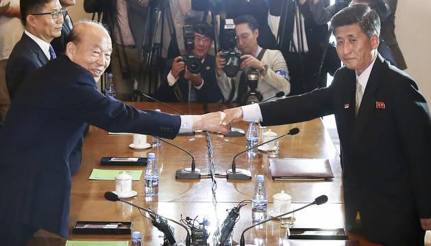 Park Kyung-seo (izda.), jefe de la Cruz Roja de Corea del Sur, estrecha la mano de Pak Yong-il (dcha.), vicepresidente del Comité para la Reunificación Pacífica de Corea del Norte, en la reunión de este viernes 22 de junio de 2018, para discutir la organización de una reunión de familias separadas por la Guerra de Corea de 1950-53 y otros asuntos humanitarios.