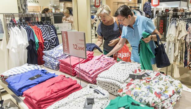 Dos mujeres examinan algunas prendas en el Corte Inglés de Pamplona, que empezó este viernes sus rebajas veraniegas.