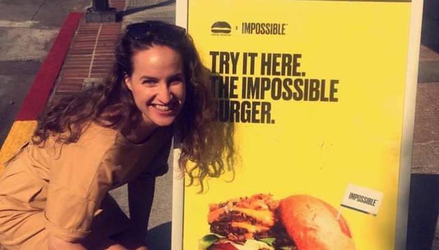 La pamplonesa Inés Resano, junto a un cartel anunciador de la hamburguesa sobre la que ella investiga.