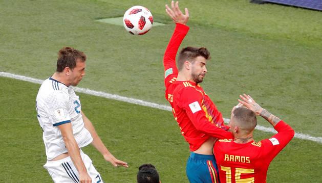 foto de Gerard Piqué comete penalti tras el remate del delantero ruso Artem Dzyuba durante el partido España-Rusia, de octavos de final del Mundial de Fútbol.