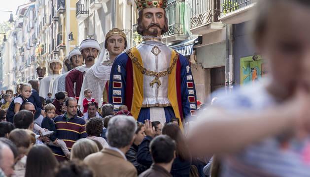 Un cabezudo de la comparsa de Pamplona se adelanta a los gigantes para perseguir a un niño.