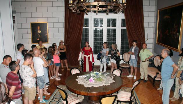 Los asistentes escuchan atentamente las explicaciones de una de las guías en una de las dependencias principales del castillo.