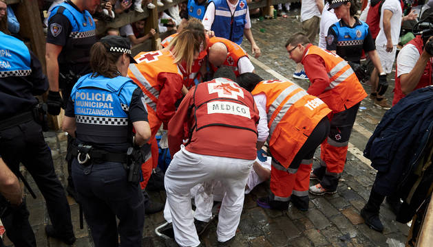 Voluntarios de la Cruz Roja atienden a uno de los heridos en el primer encierro de los Sanfermines 2018.