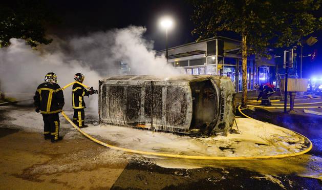 Bomberos trabajan en la extinción de un incendio en un vehículo durante unos disturbios en Nantes (Francia) el 3 de julio de 2018.