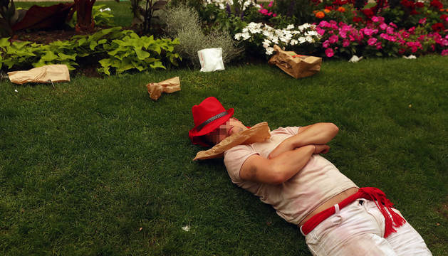 Un joven, dormido en uno de los jardines de Pamplona